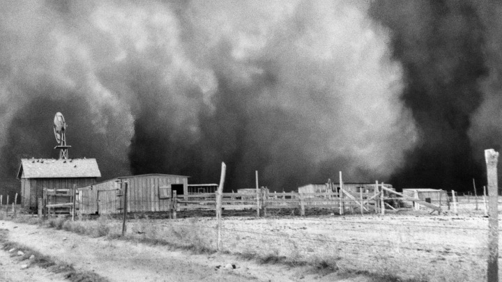 Farm with huge dust cloud approaching, dust storm near barn. April 15, 1935. Boise City, Oklahoma.